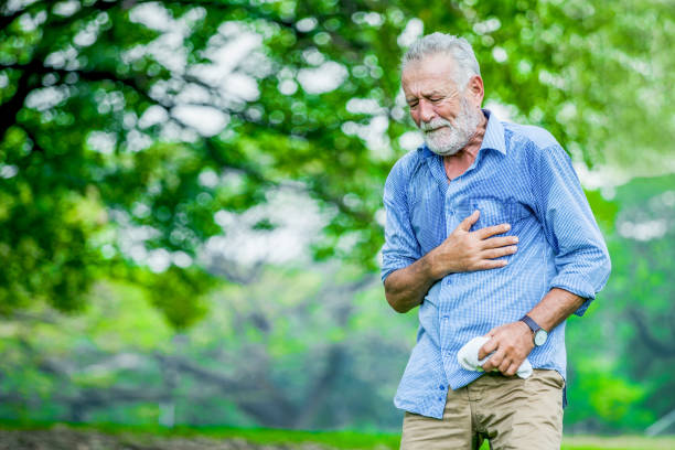 Heart attack concept. Senior man suffering from chest pain outdoor in park, stock photo