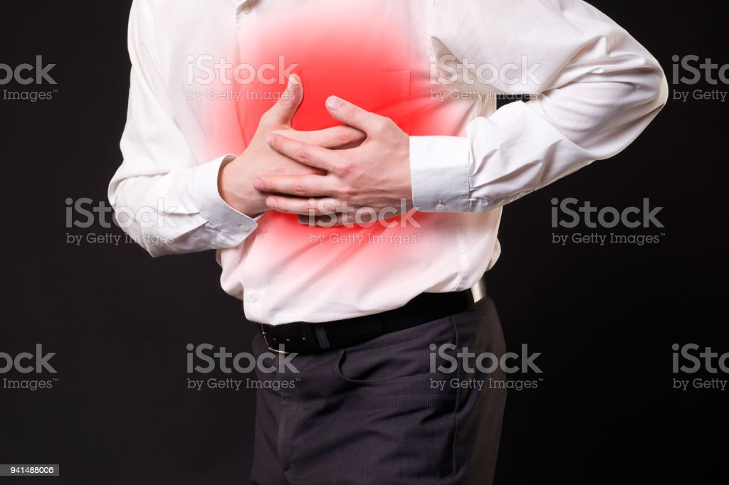 Heart attack, man with chest pain on black background stock photo
