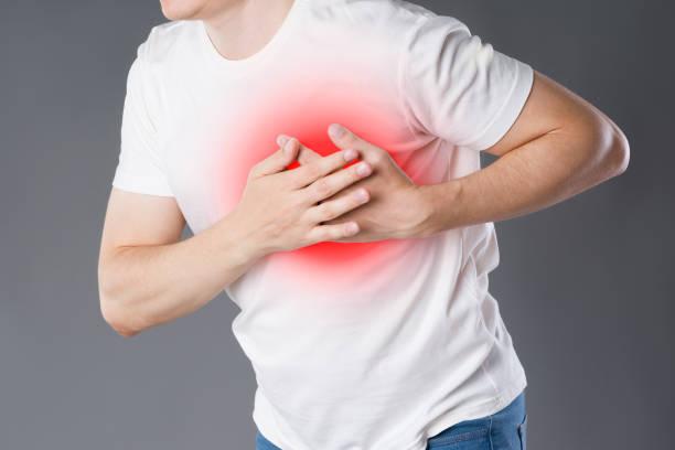 herzinfarkt, mann mit schmerzen in der brust auf grauem hintergrund - herz lungen training stock-fotos und bilder