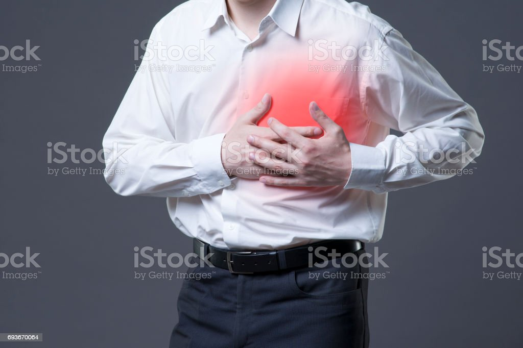 Heart attack, man with chest pain on gray background stock photo