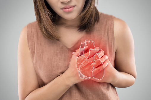 The photo of heart is on the woman's body, Severe heartache, Having heart attack or Painful cramps, Heart disease, Pressing on chest with painful expression.