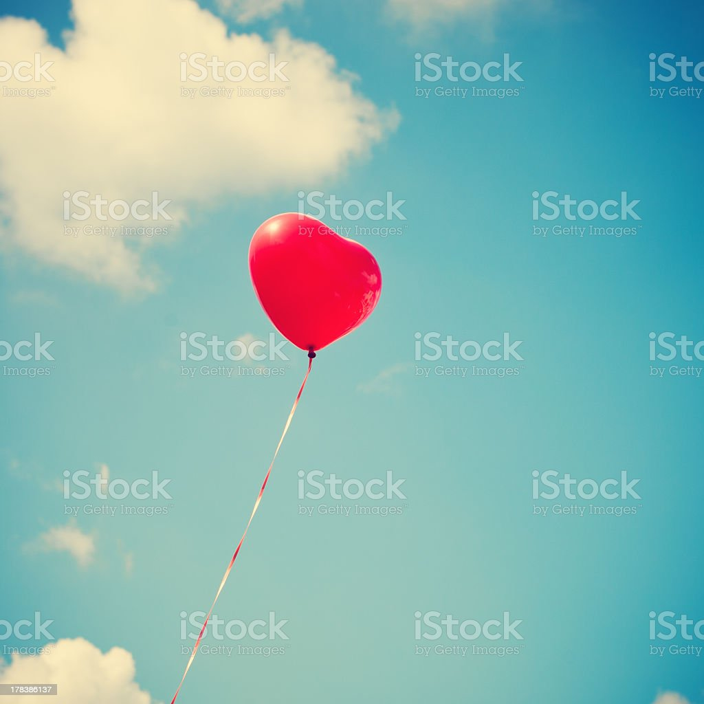 Heart balloon on blue sky with some clouds in a retro filter stock photo