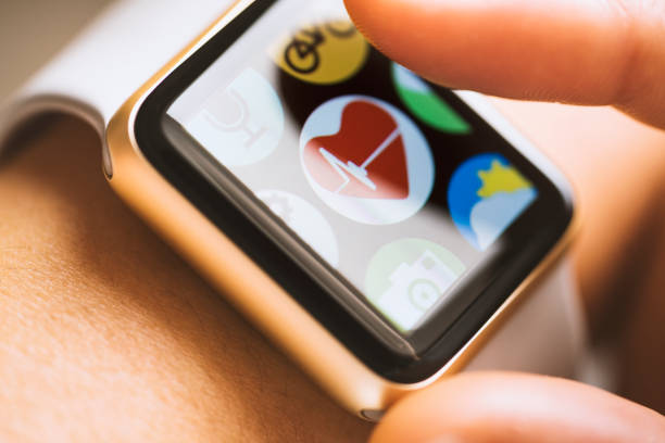 Heart beat application on smart watch touchscreen Close up shot of woman wrist wearing smart watch.  Finger touching appwith heart beat icon on touchscreen. fitness tracker stock pictures, royalty-free photos & images
