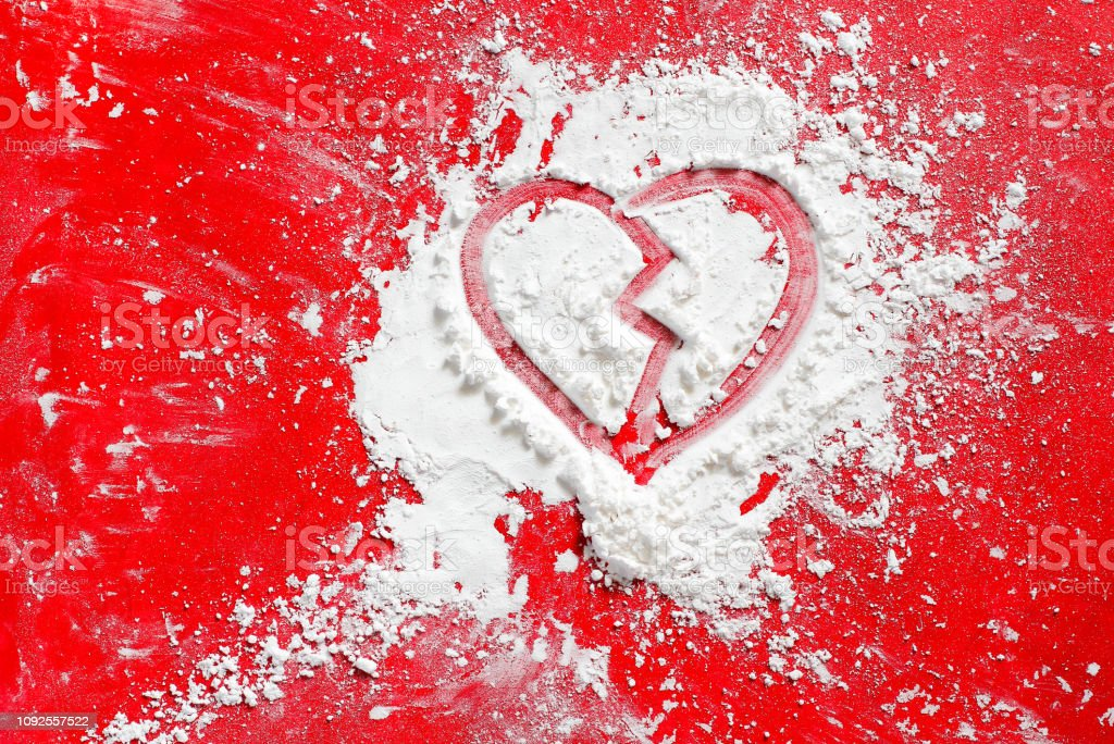 Valentine\'s day heart broken sign with white icing flour, on red...