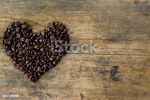istock Heart chape from coffee beans. Lovely heart chape by roasted coffee beans on rustic wood table. Love theme concept with coffee beans for Valentine's background and wallpaper. Heart chape background. 694135096