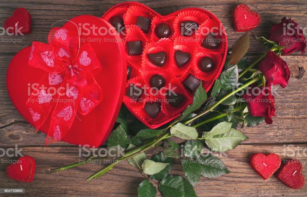 Heart chocolate box and red roses on wooden rustic background royalty-free stock photo