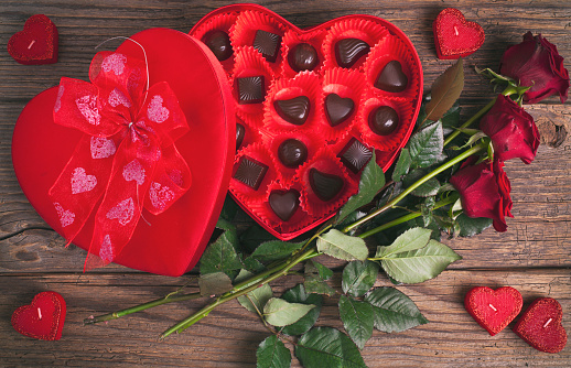 Heart chocolate box and red roses on wooden rustic background