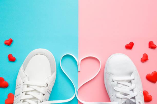 herz aus weißen schnürsenkel zwischen männlichen und weiblichen sportschuhe erstellt. helle, rote herzen. liebe-konzept. leeren platz für schöne, niedliche text, zitat oder sprüche auf pastell blau und rosa papier. closeup. - schnürsenkel stock-fotos und bilder