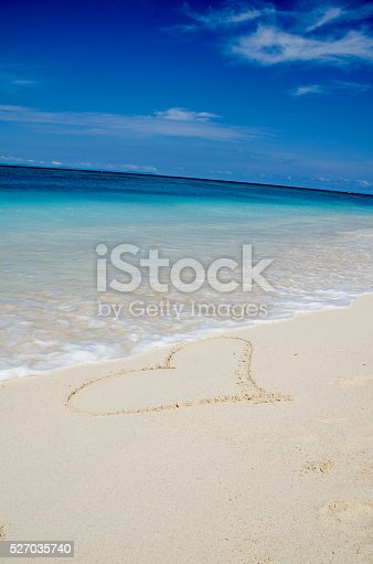 istock Heart Drawing in the White Sand Tropical Beach 527035740