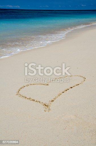 istock Heart Drawing in the White Sand Tropical Beach 527035894