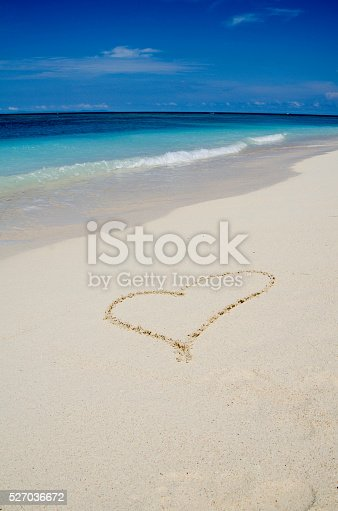 istock Heart Drawing in the White Sand Tropical Beach 527036672