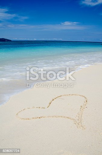istock Heart Drawing in the White Sand Tropical Beach 528057724