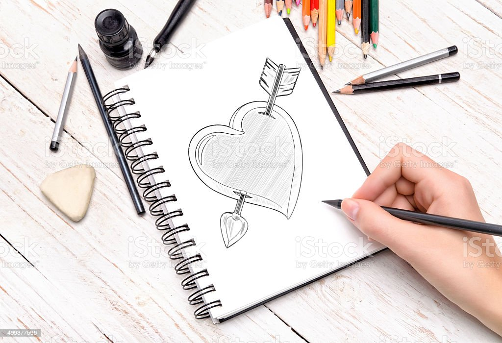 Heart drawn in pencil on a paper sheet stock photo