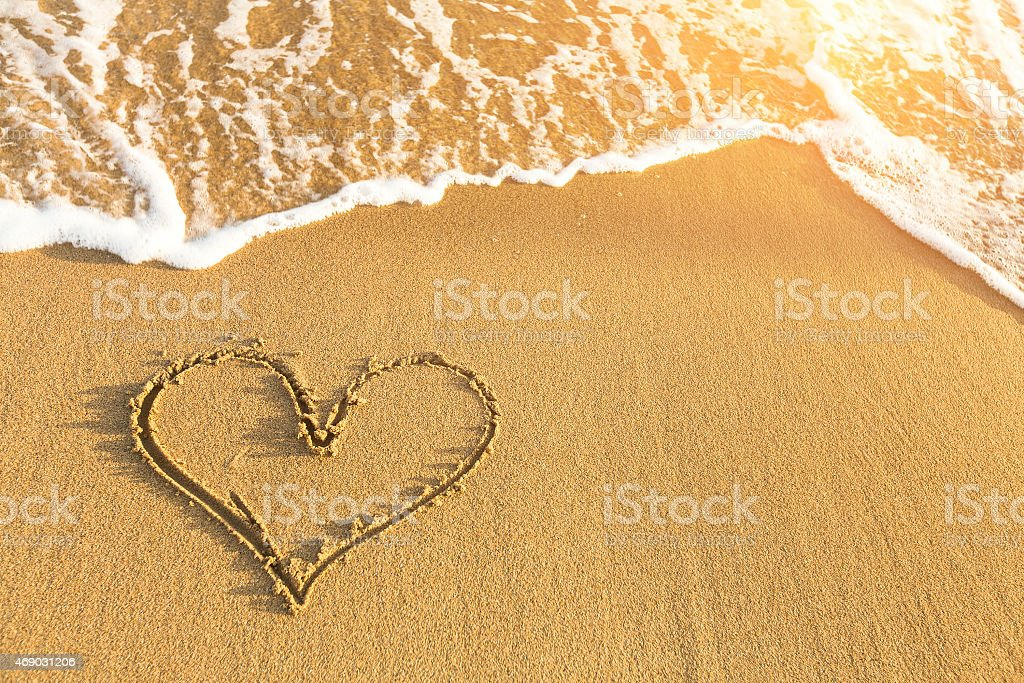 Heart drawn in sea beach sand, soft wave. stock photo