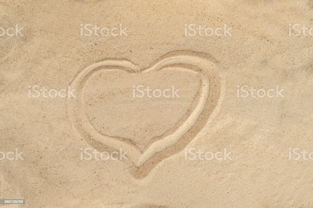 Heart drawn in the sand. Beach background. Top view royalty-free stock photo