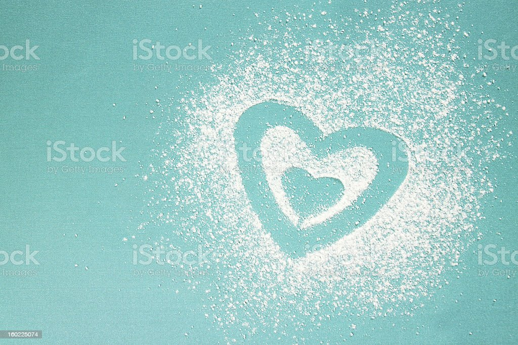 Heart drawn in white powdery substance on blue background stock photo