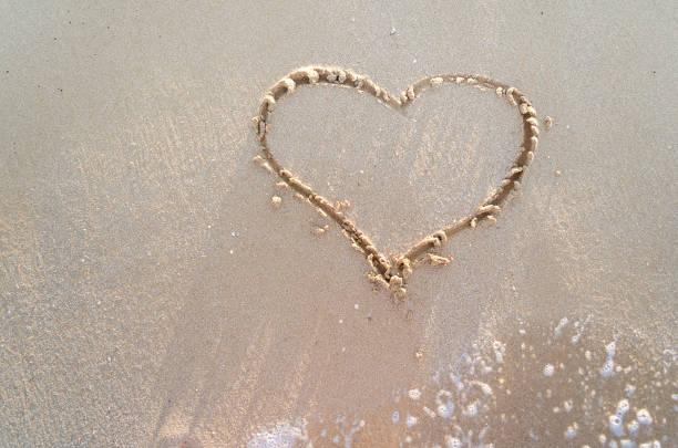 Heart drawn on a sand of beach stock photo