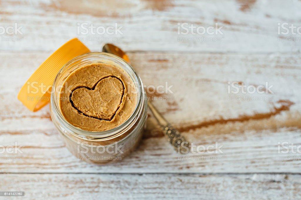 Heart drawn on peanut butter in glass jar stock photo