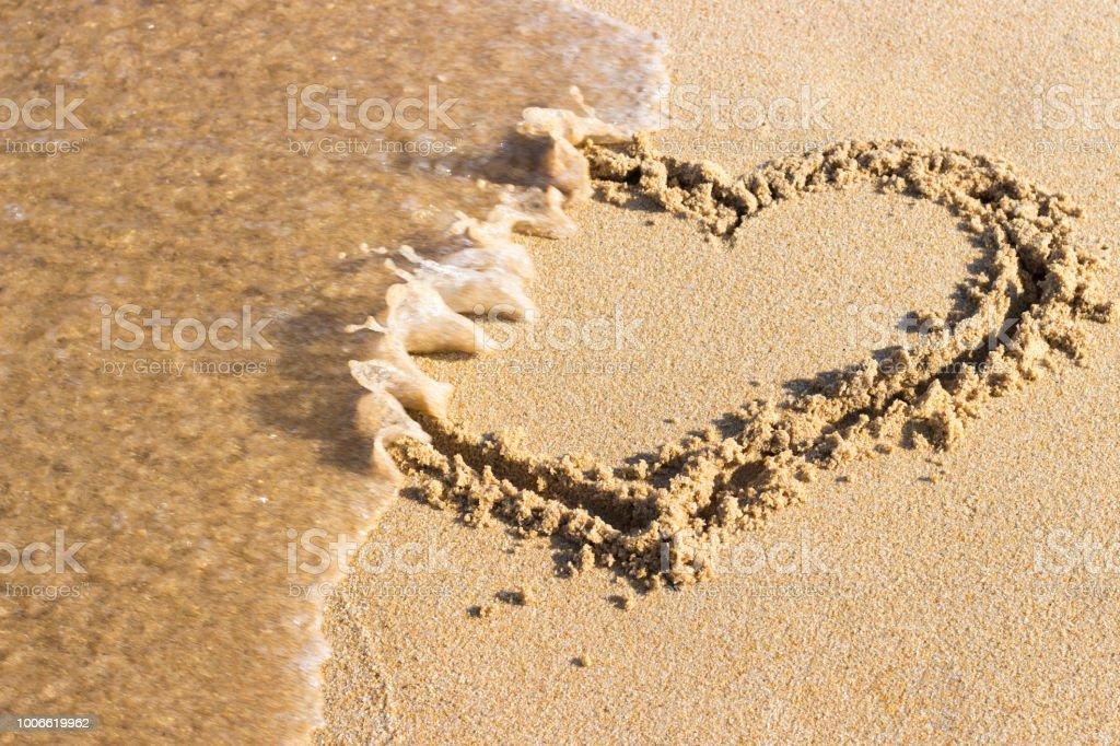 砂に描かれたハートは海の波、平面図・ エンドのリレーションシップによって洗浄されます。 ストックフォト