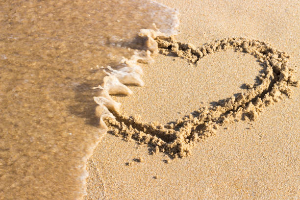 heart drawn on sand is washed off by sea wave, top view End relationship. heart drawn on sand is washed off by sea wave, top view End relationship. relationship difficulties stock pictures, royalty-free photos & images