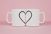 Heart drawn on two cups on pink background