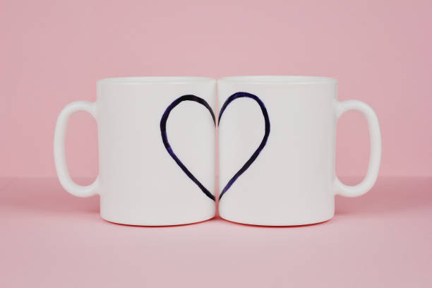 heart drawn on two cups on pink background - i love you stock photos and pictures
