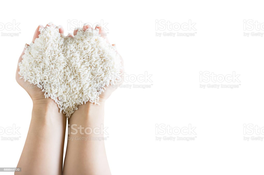 heart form of Grain white rice in woman's hands stock photo