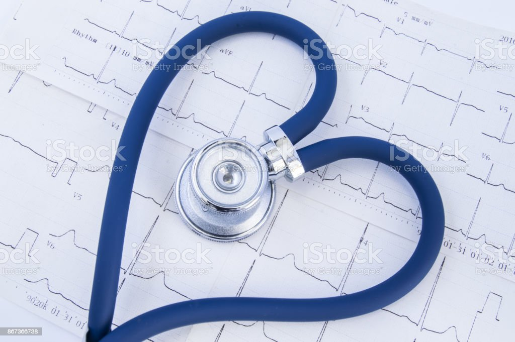Heart formed stethoscope against background of electrocardiogram (ekg). Head or chestpiece and flexible tubing of blue stethoscope folded into heart shape, which lies on printed electrocardiogram stock photo