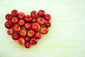 A heart from ripe red apples on the green wooden background, top view.