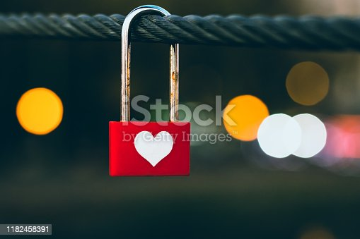 Heart hanging on clothesline at night. Red padlock on a rope, bokeh of evening city lights. Symbol of love. Romantic concept