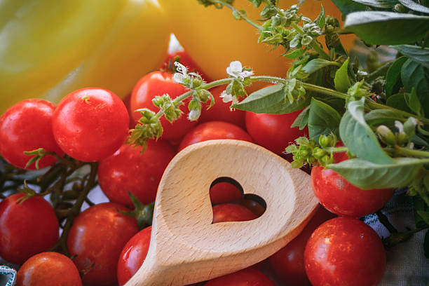 Heart hole spoon and vegetables stock photo