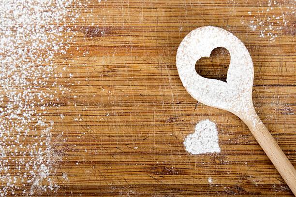 heart loch löffel auf der hölzernen gebäck und -brett - löcherkuchen stock-fotos und bilder