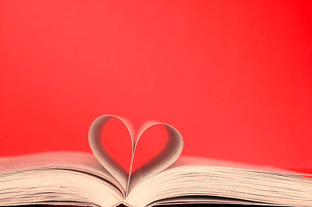 Heart in book from sheets at red background stock photo
