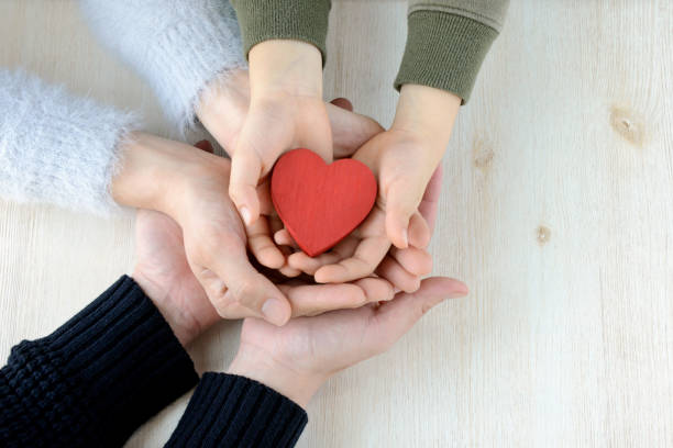 heart in famiy hands - blood donation stock pictures, royalty-free photos & images