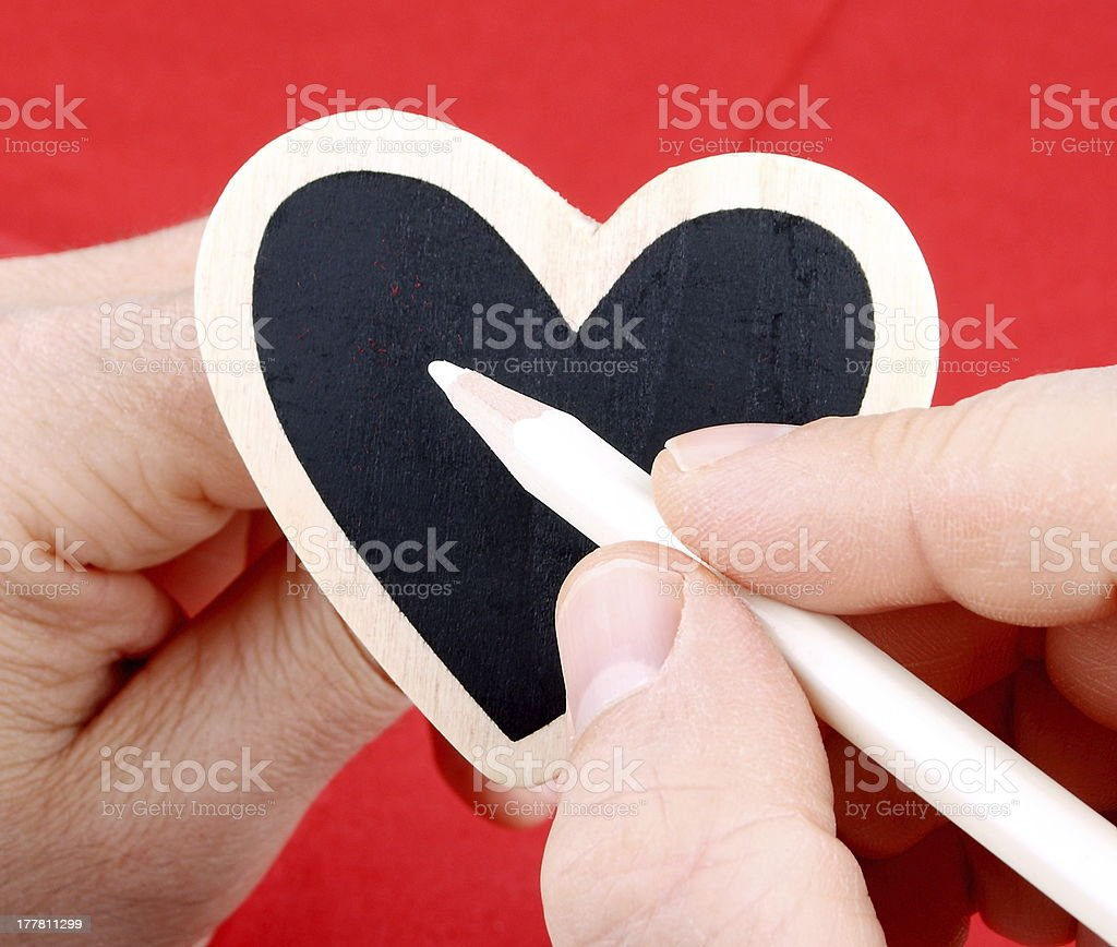 Heart in hands inscribed with white chalk on red background royalty-free stock photo
