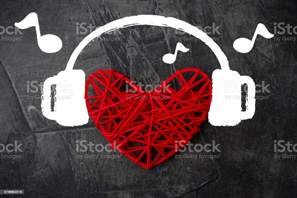 Heart in headphones on a dark background. Theme for Valentine's Day. Wedding, love stock photo