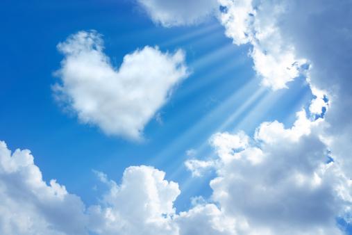 heart shaped cloud in cloudy sky  and sunbeam.