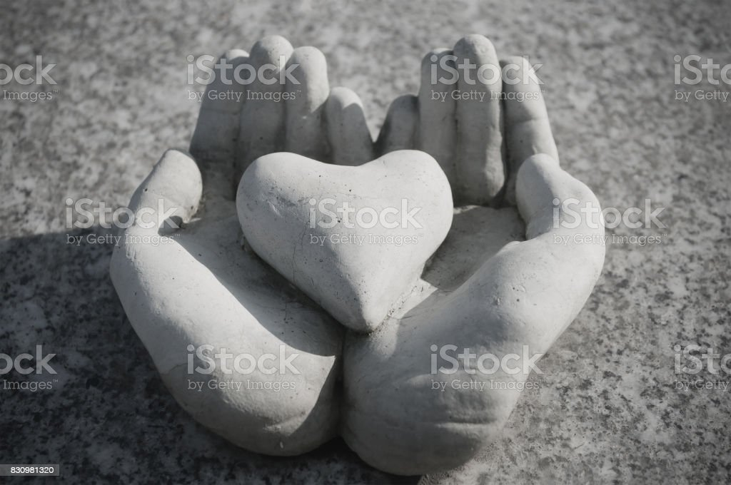 heart in stoned hands in cemetery on a tomb stock photo