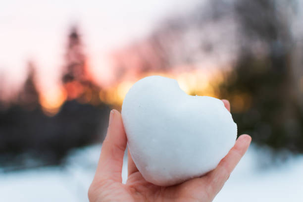 Heart in sunset winter wonderland love conceptual heart shaped snowball with pink sky stock photo