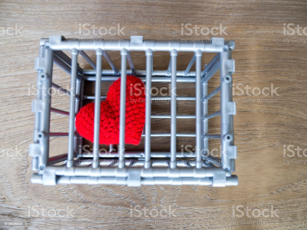 Heart in the cage Put on a wooden table, It shows the closure of freedom and love. Love is disappointed and not satisfied. Closing and blocking in love ...