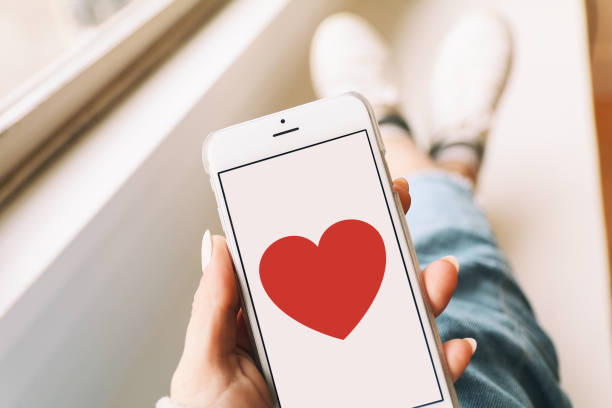 Heart & love on a mobile phone A smartphone with a red heart on the display held by a woman. date stock pictures, royalty-free photos & images