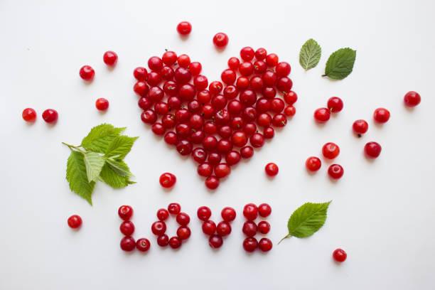 herz aus kirschen. rote kirschen auf weiß sind mit dem wort liebe gefüttert. - herz zitate stock-fotos und bilder