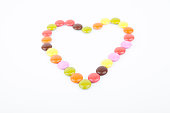 Heart made of colored candies on a white background.