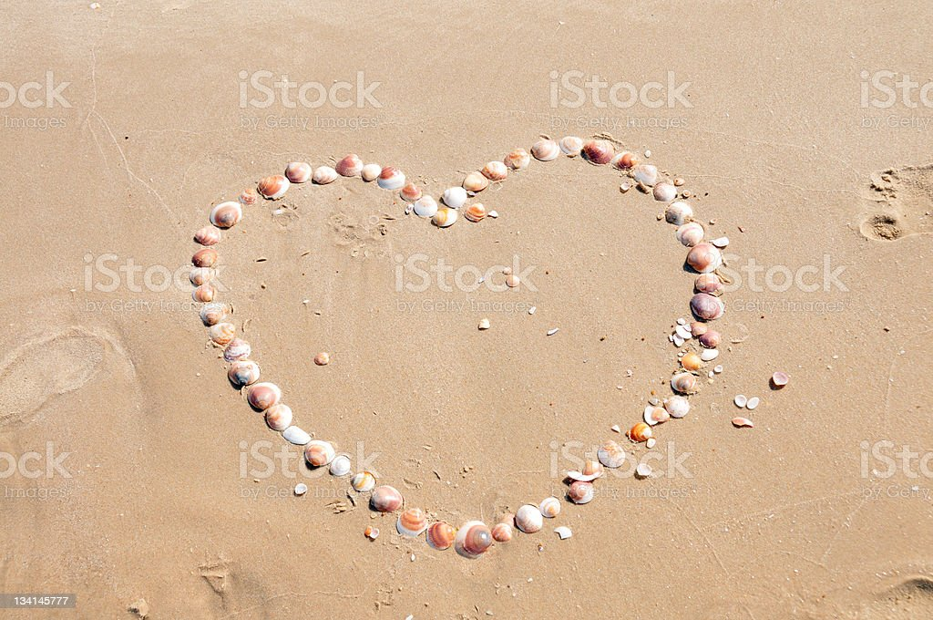 heart made of sea shells in the sand.