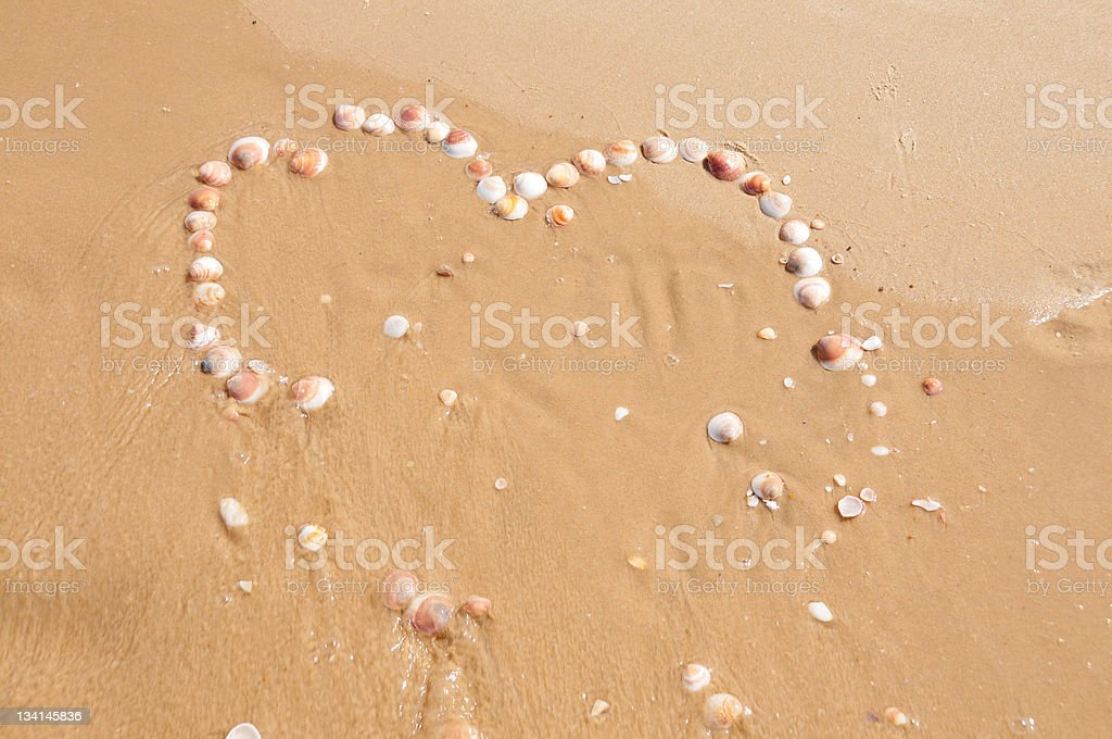 heart made of seashells in the sand. royalty-free stock photo