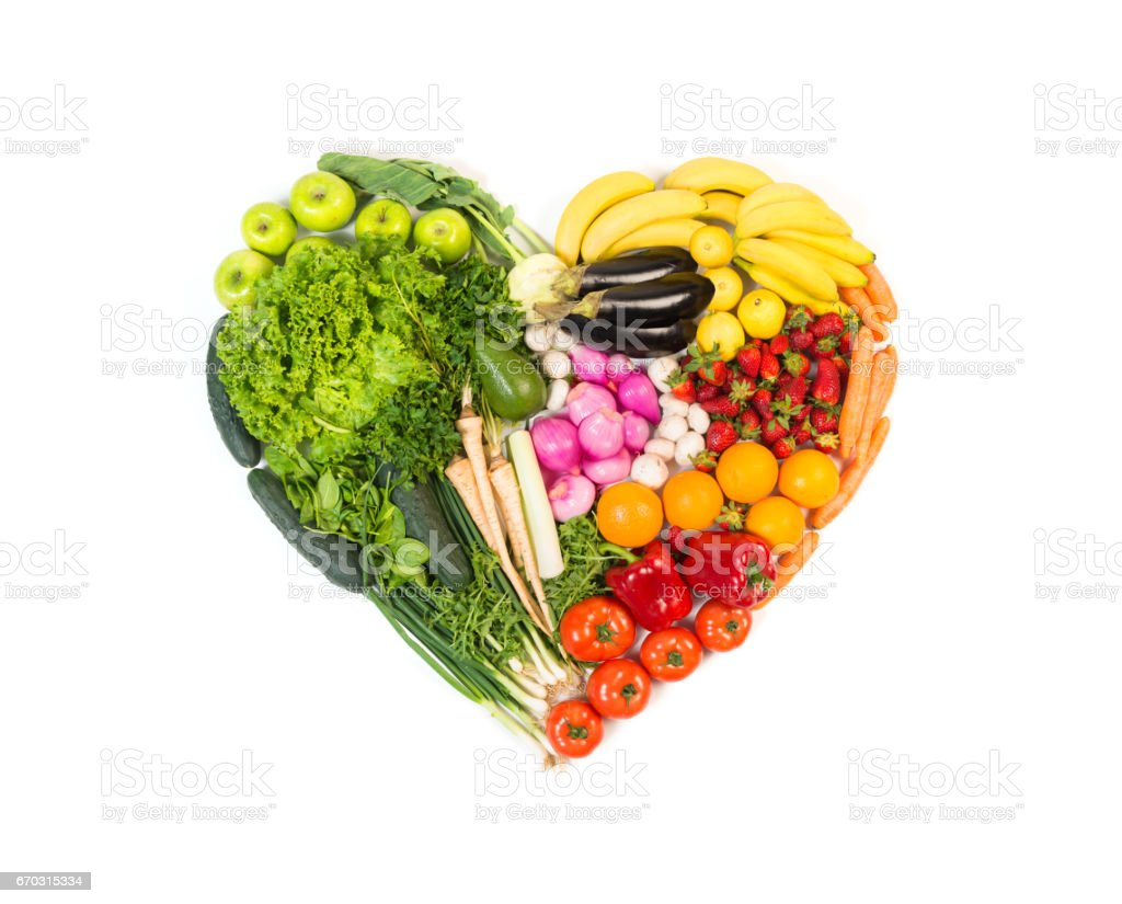 Heart made out of fruits and vegetables isolated on white background stock photo