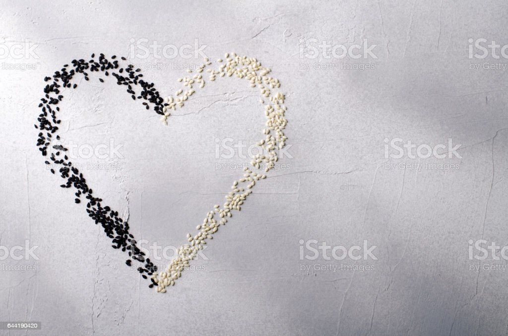 Heart made with black and white sesame seeds, on gray background. Love, Valentine's day concept. Top view, copy space. stock photo