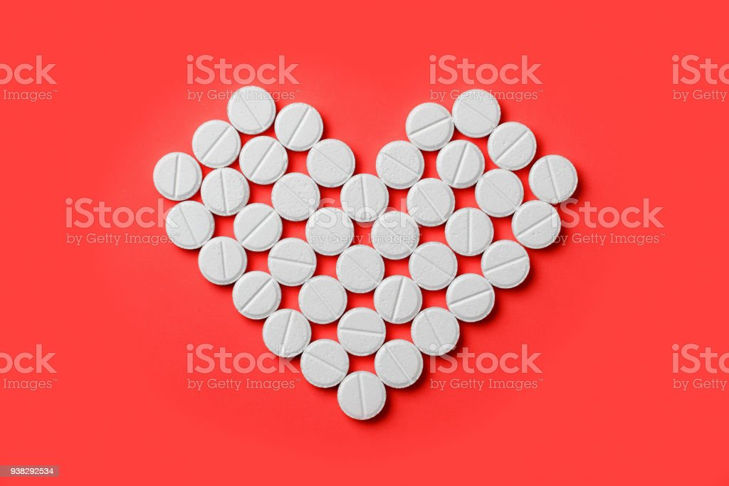 Heart medications on a red background stock photo