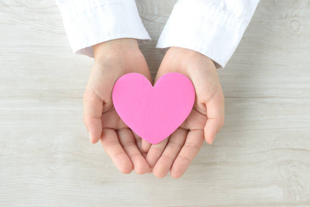Heart object covered by child's hands stock photo