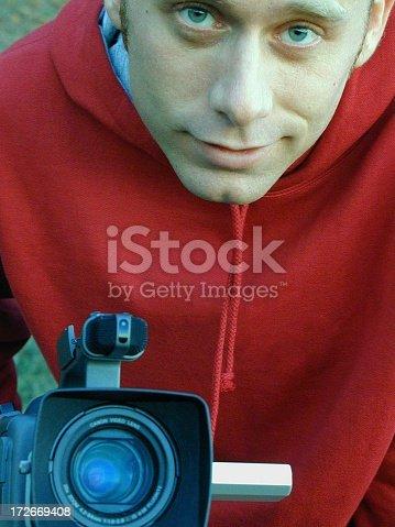 Man posing with his pet video camera.